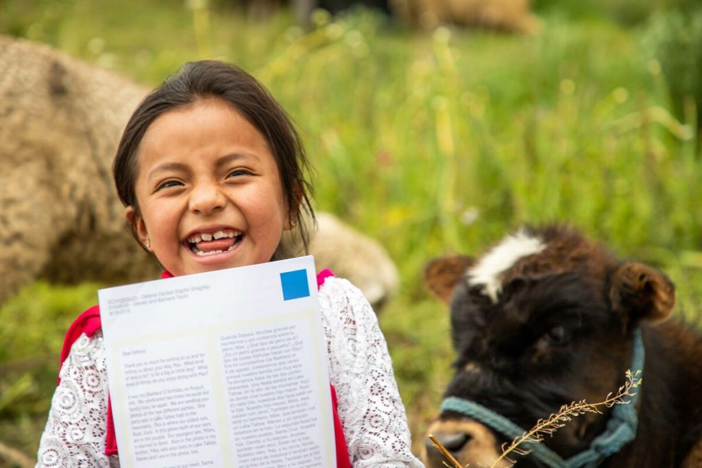 Little girl holds her letter up to the camera, and a cow is in the corner.