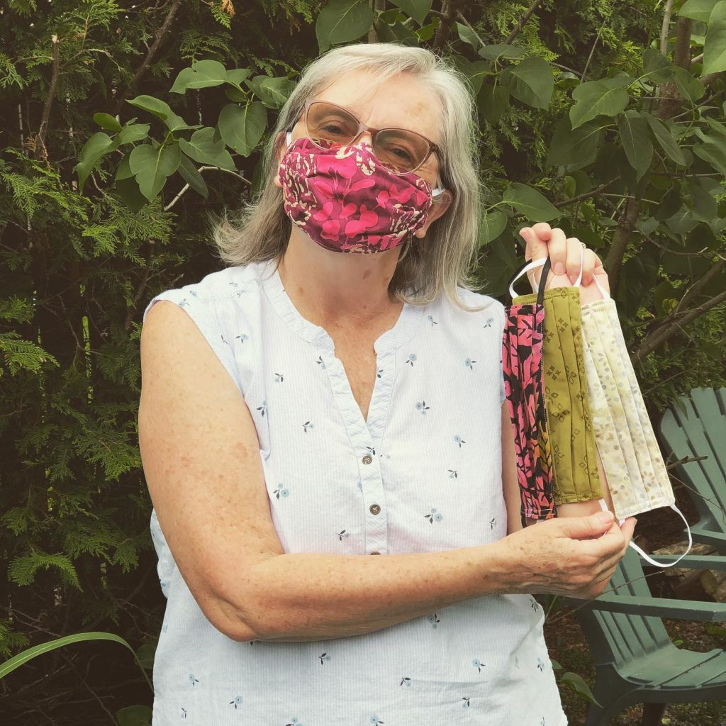 Woman wearing a white shirt wears a pink mask and holds up 3 other masks she has made