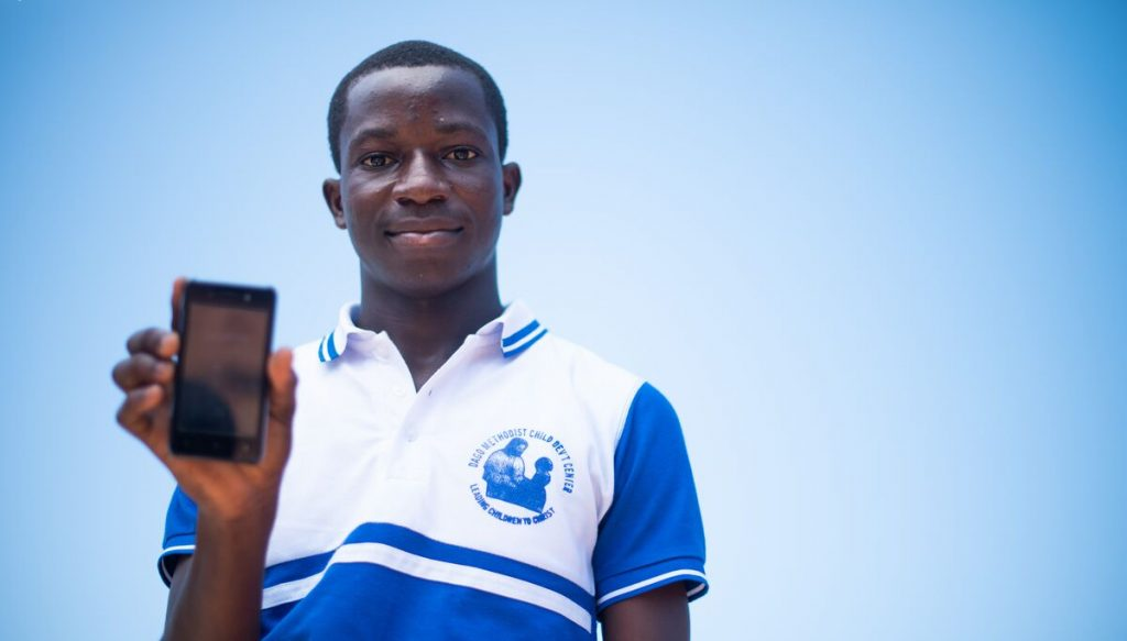 Young man wearing a blue and white collard shirt holds a cell phone facing the camera