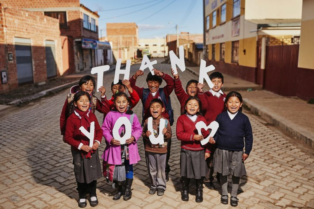 "A group of kids hold up letters that say ""thank you"""
