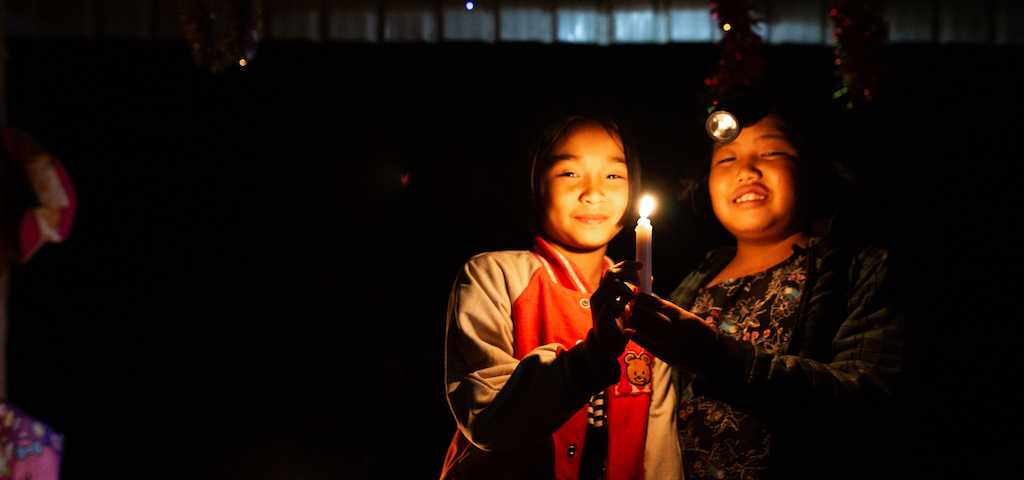 Two girls stand in candlelight.