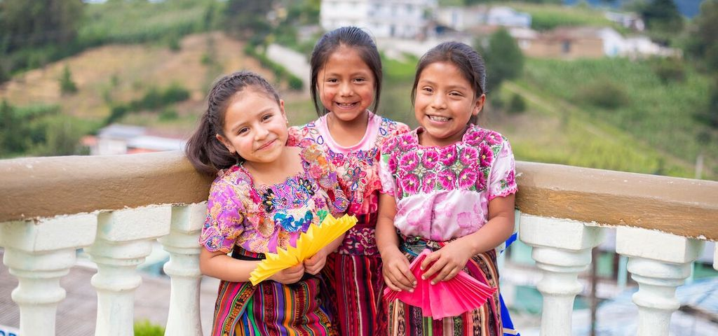 Three girls in traditional Guatemalan dresses.