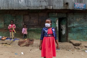 Shaniz in the streets of Mathare, wearing a red dress and a white face mask.
