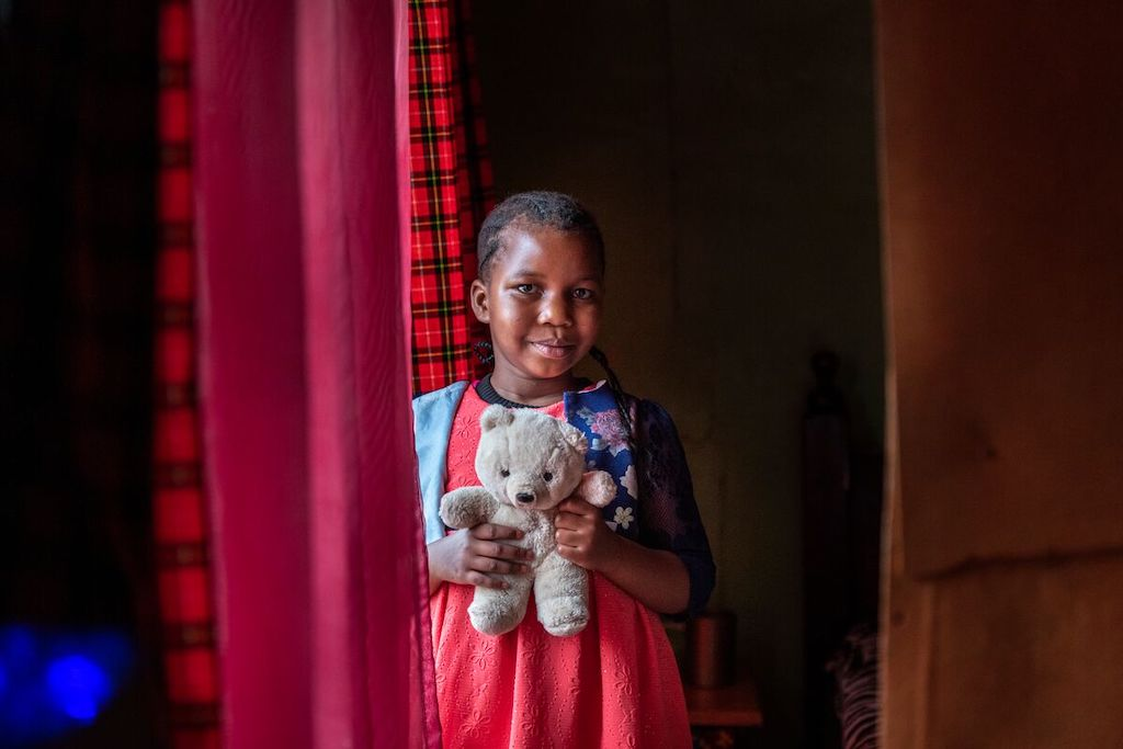 A portrait of Shaniz, holding her teddy bear.