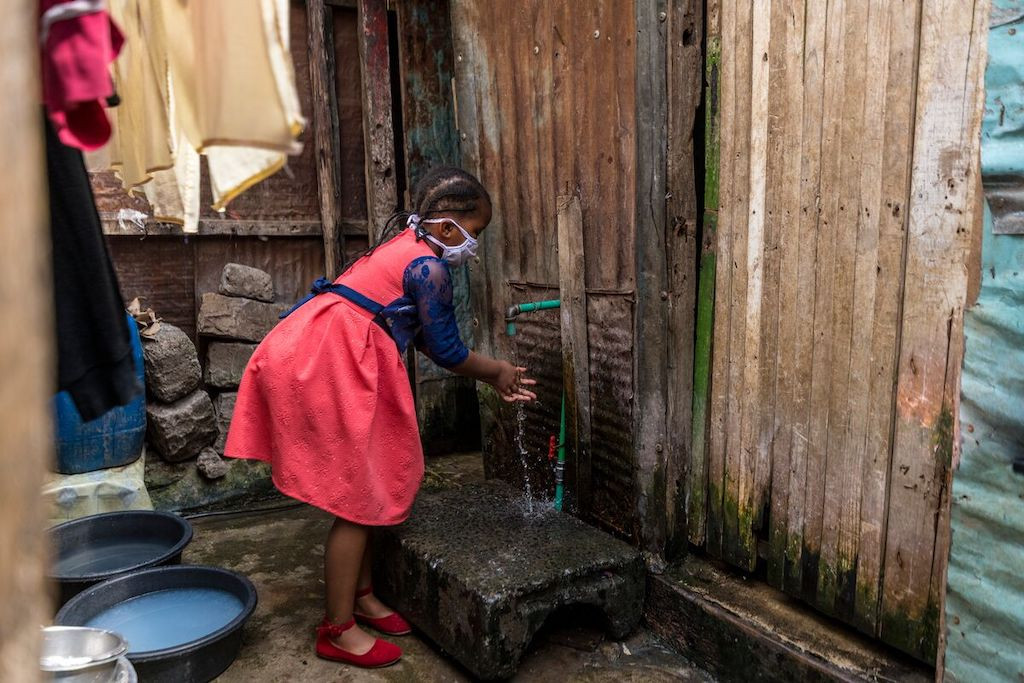 Shaniz at an outdoor tap washing her hands.