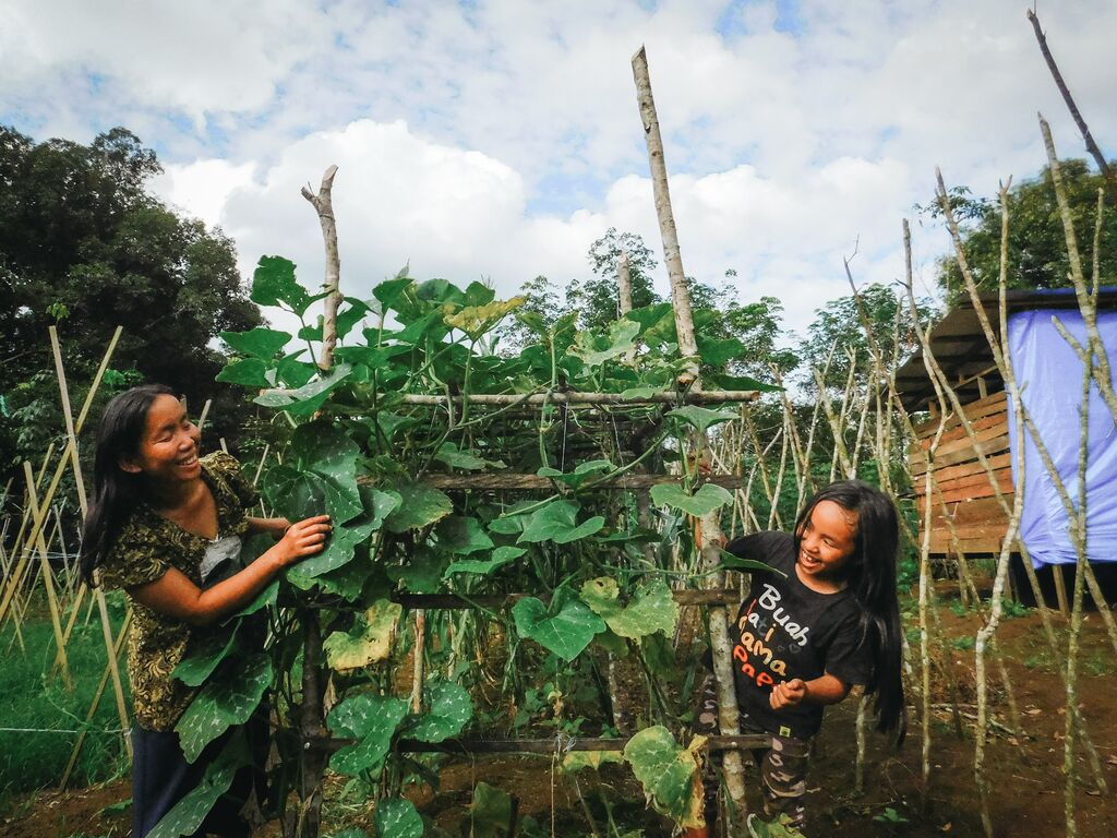 Meisy and her mom, Lusiana, working in their bean garden.