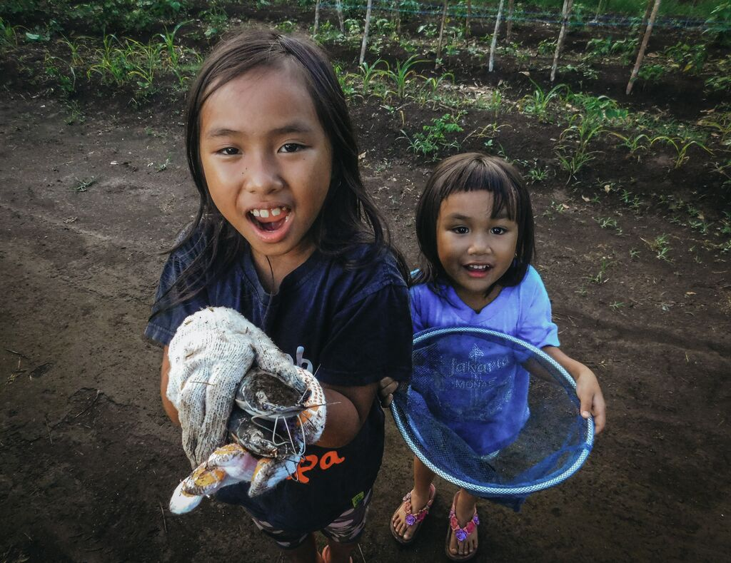 Meisy and her little sister look up at the camera holding fish and nets.