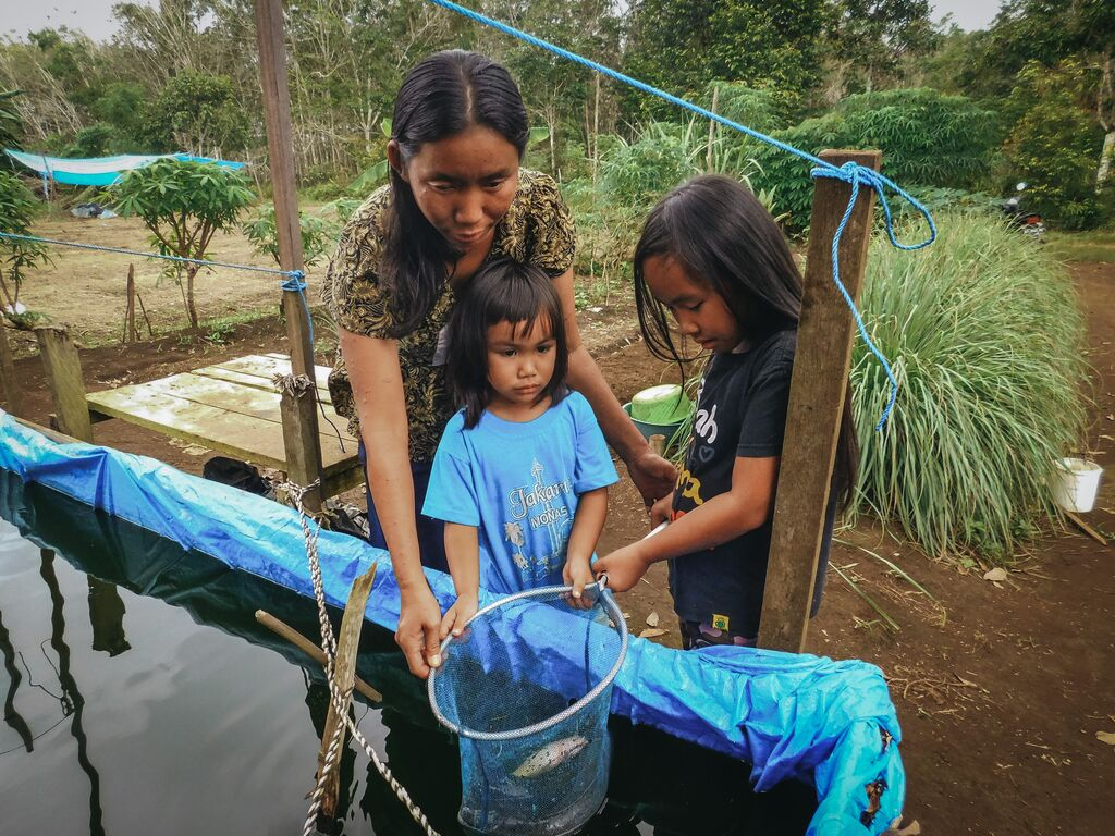 Meisy and her sister and mom gather around the pond with a net to catch fish.