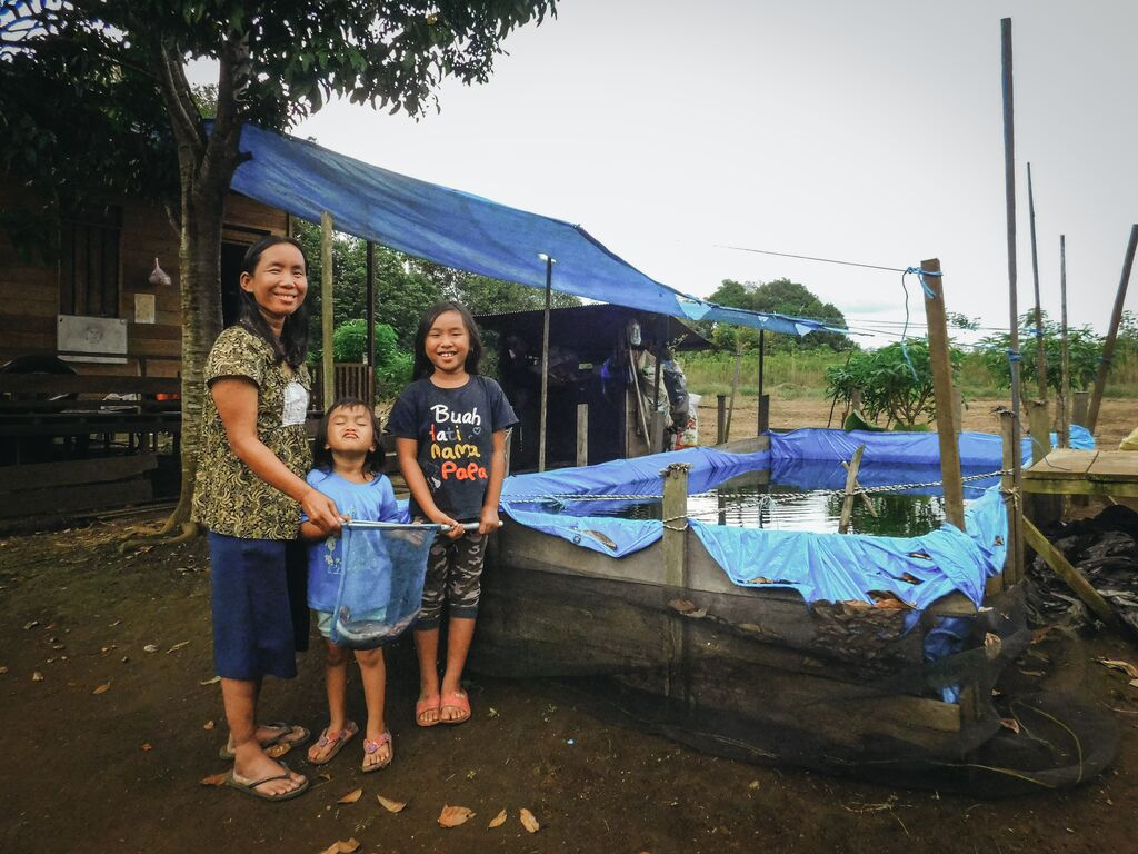 The family poses infront of their fish pond.