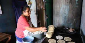 A women sits infront of a large griddle and makes tortilla's