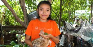 A teenage girl holds a chicken in her arms. She feeds the chicken from her hands.