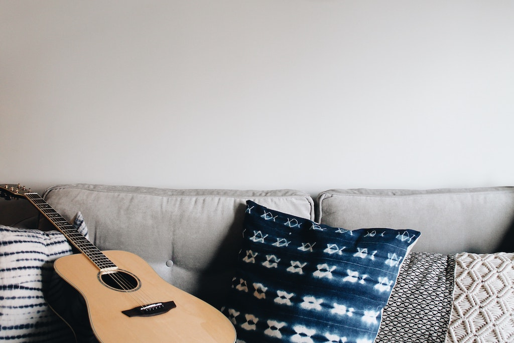 An acoustic guitar lies on a beige couch with different cushions.
