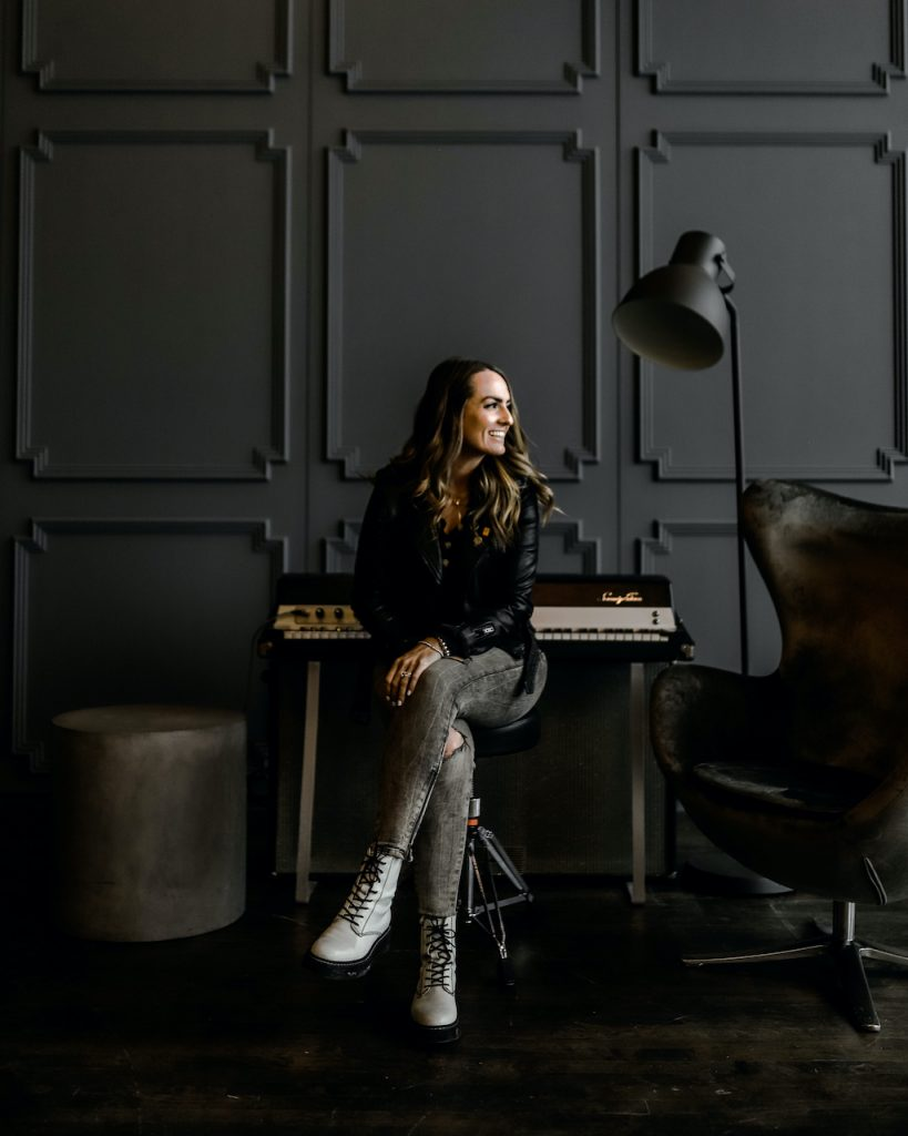 Brooke is pictured sitting by a piano in a black painted room.