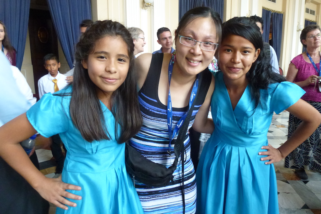 Andrea poses with two girls in El Salvador, they are all wearing blue dresses.