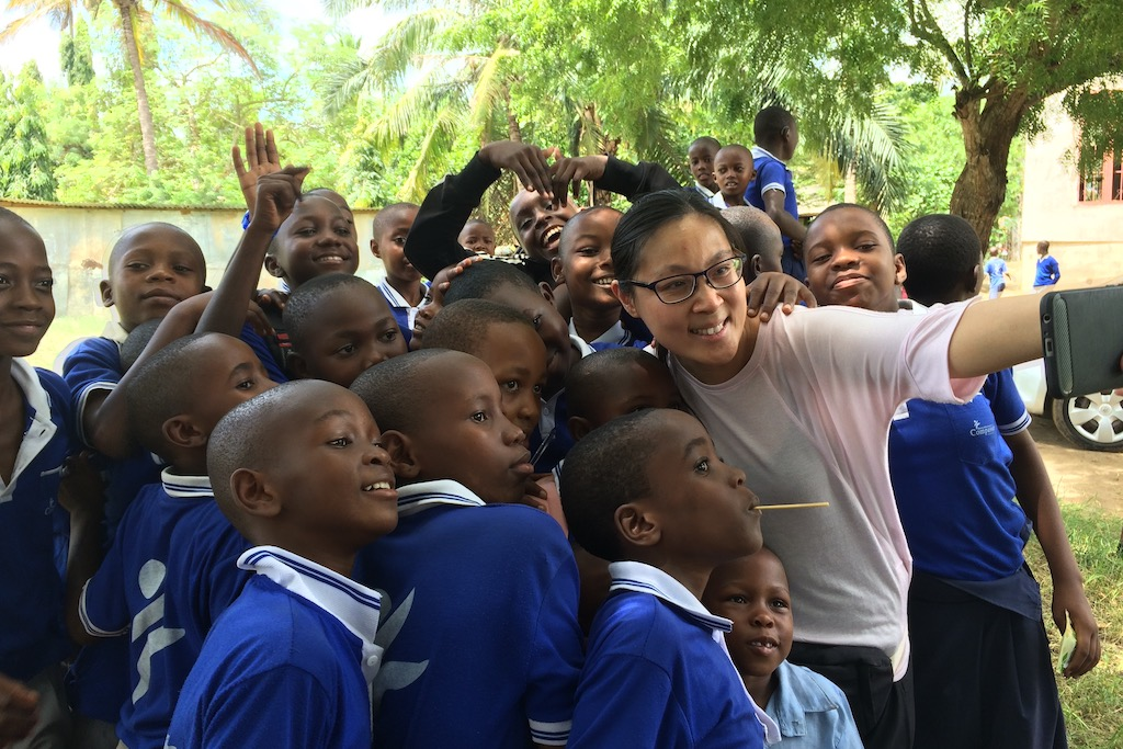 Andrea stands amongst a group of children in blue school uniforms, taking a selfie with the group.