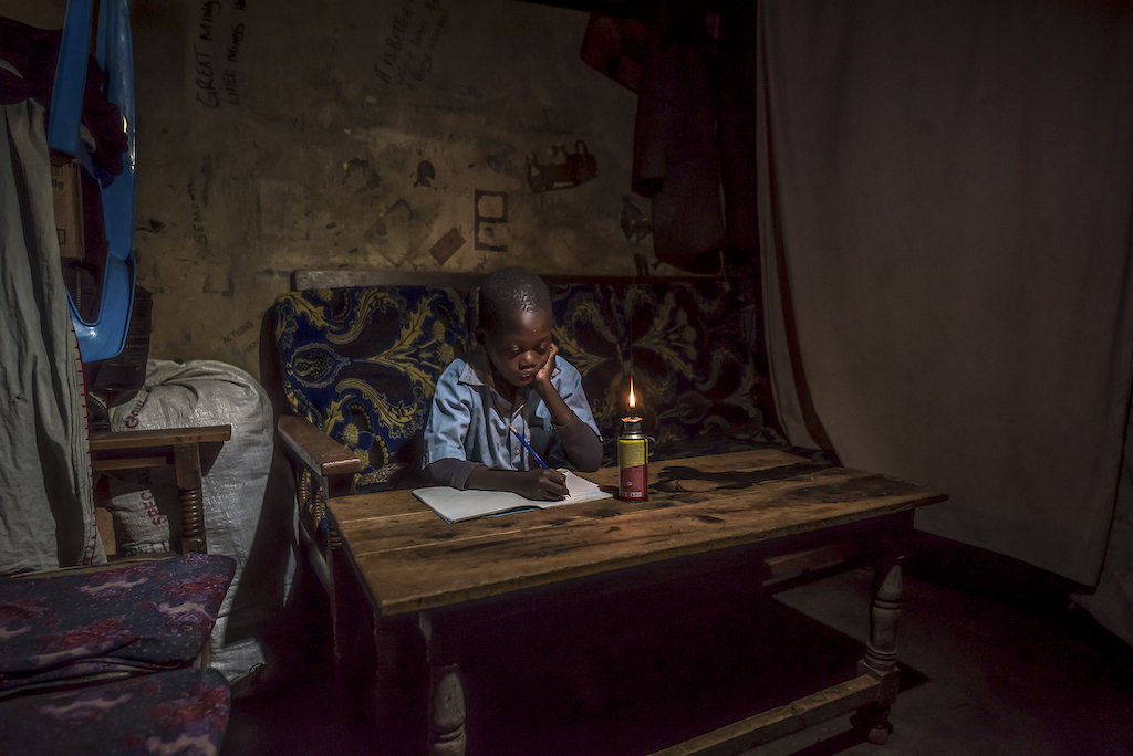 A young boy sits at a wooden table with a notebook in front of him and a kerosene lamp lit nearby.