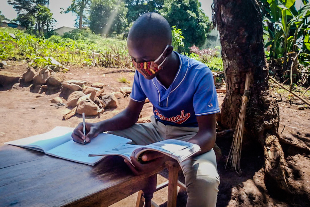 Wearing a cloth protective face mask, Emmanuel sits at a table under a tree, writing in a notebook.
