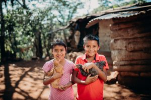 A boy and a girl standing next to each other, each holding a chicken.