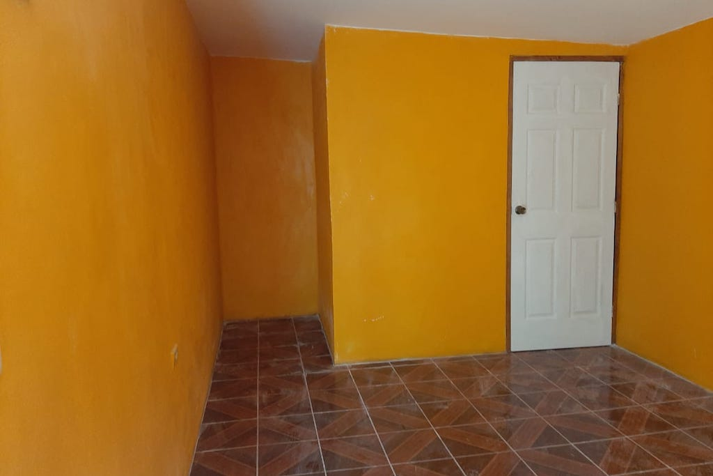 The interior of Francis' new bedroom. The walls are bright yellow and the floors are brown tile.