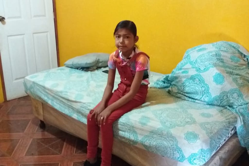 Francis is earring a t-shirt and pink overalls, sitting on a bed in her new room, which is painted bright yellow.