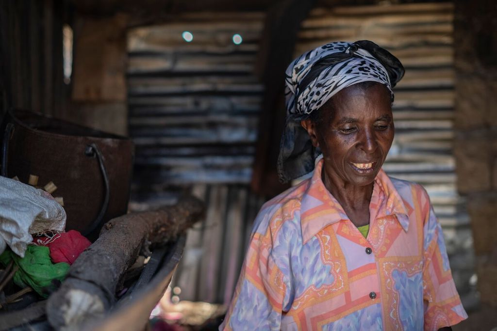 Nkatha stands in her home, wearing a black and white headscarf and a patterned peach shirt.