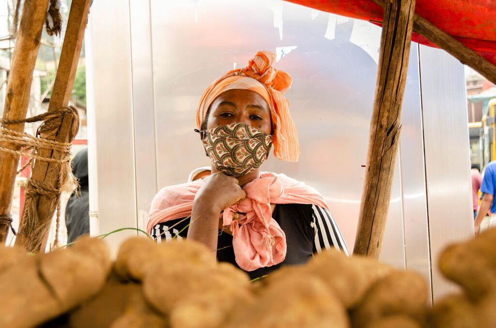 Hanna stands in front of a potato stand, wearing a mask on her face and looking at the camera