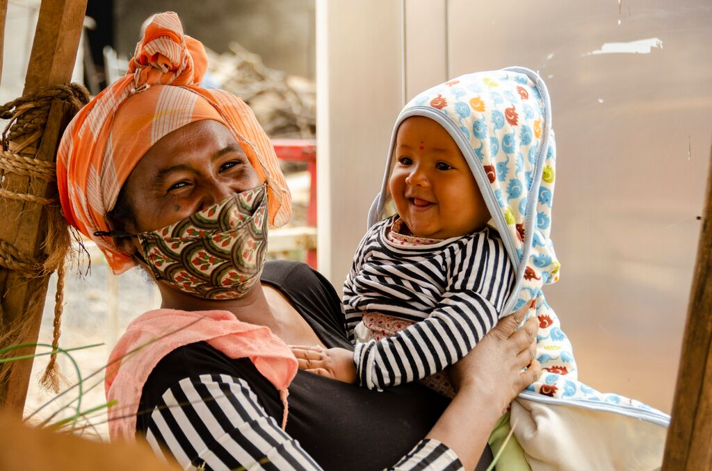 Hanna wears a masks and smiles holding her baby boy, Mikyas, who is wearing a blue hood and a stripped shirt.