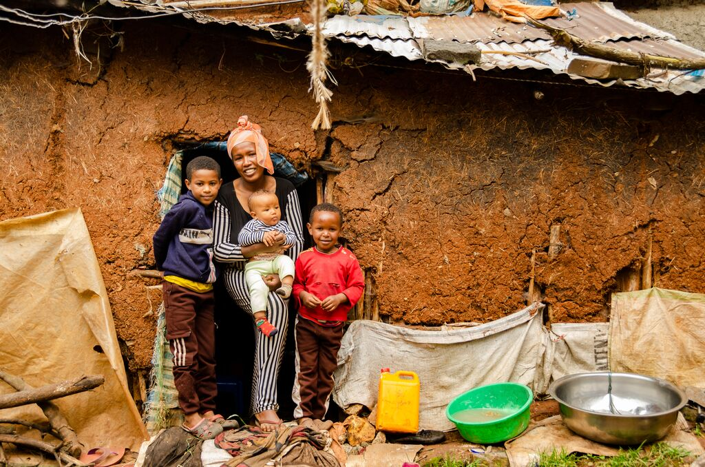 Hanna and her 3 children stand in the doorway of their home