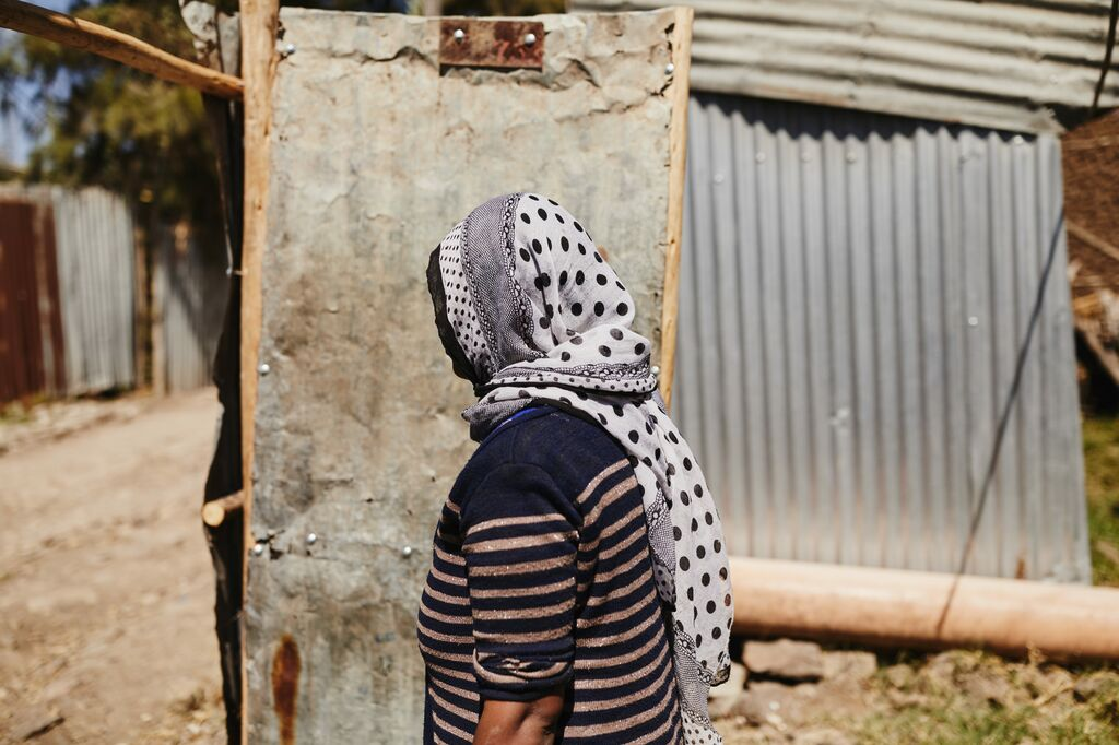 A woman with a scarf around her head walks through metal doors.