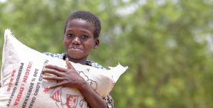A boy from Burkina Faso holds a large bag of rice. He stands in a walled yard surrounded by trees.
