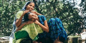 A teenage girl, from Bangledash laughs and lies her head on her mother's lap. They both wear, bright, patterned dresses and her mother wears a bright scarf on her head.
