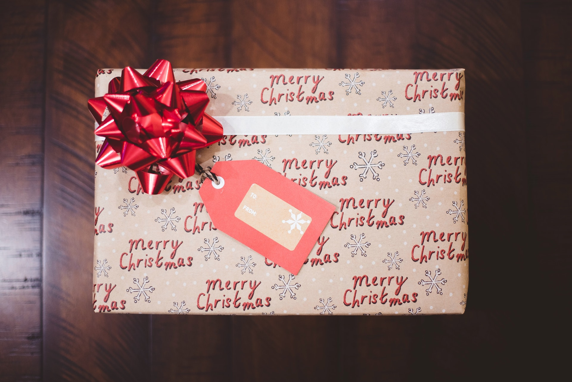 A wrapped Christmas gift with a red bow and wrapping paper that says Merry Christmas