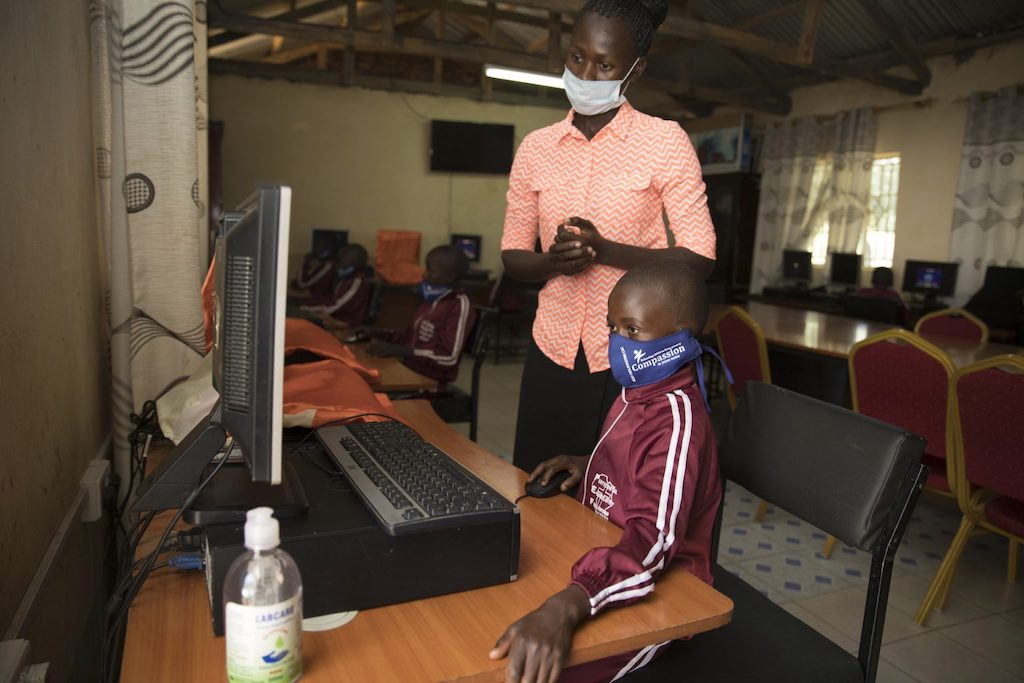 A young student works at a computer with a teacher standing behind her. Both are wearing protective face masks.