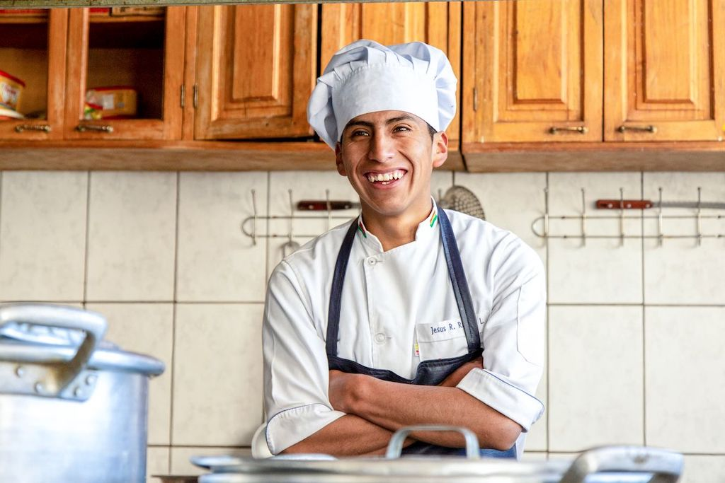 A young man in a chef's uniform standing in a kitchen.