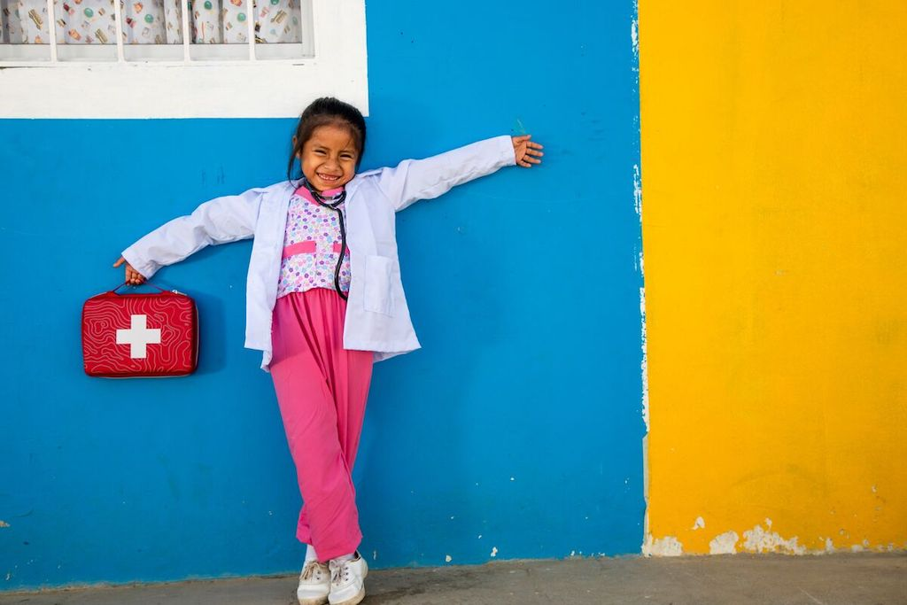 A young girl standing against a blue and yellow wall dressed as a doctor