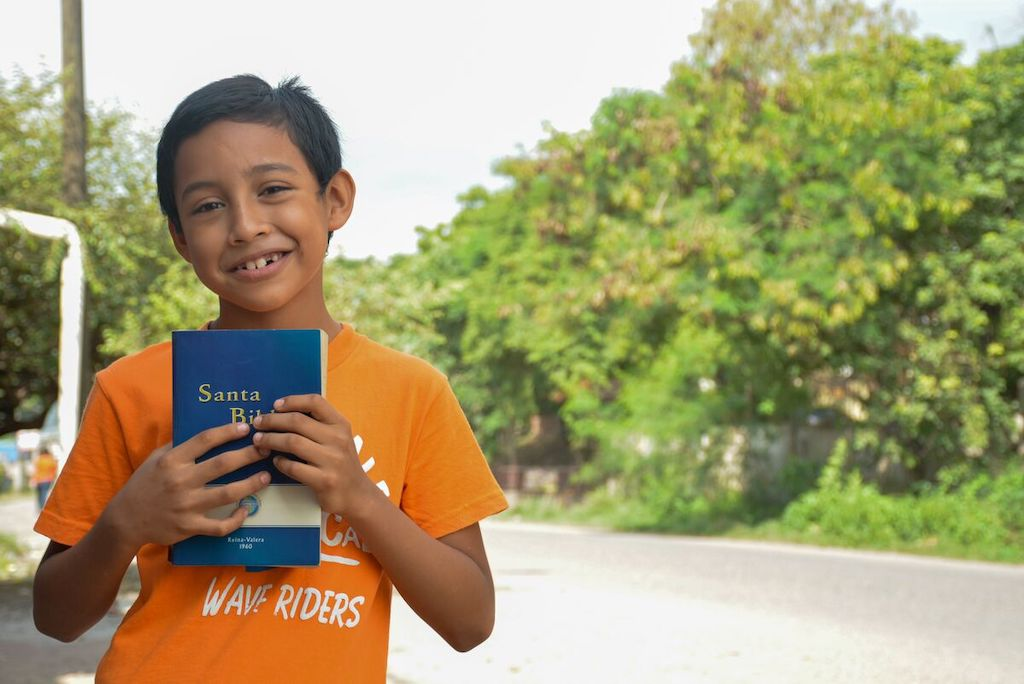 A boy wearing an orange shirt holds a Bible to his chest.