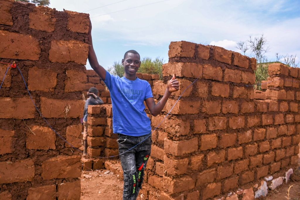 A teenage boy in Rwanda stands amongst unfinished brick walls that will make up his family's new home.