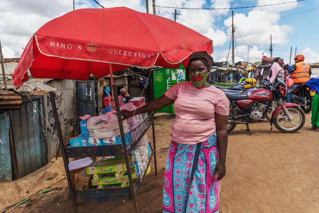 A woman in a pink shirt and patterned face mask stands at a stall under a red umbrella, selling consumer items.
