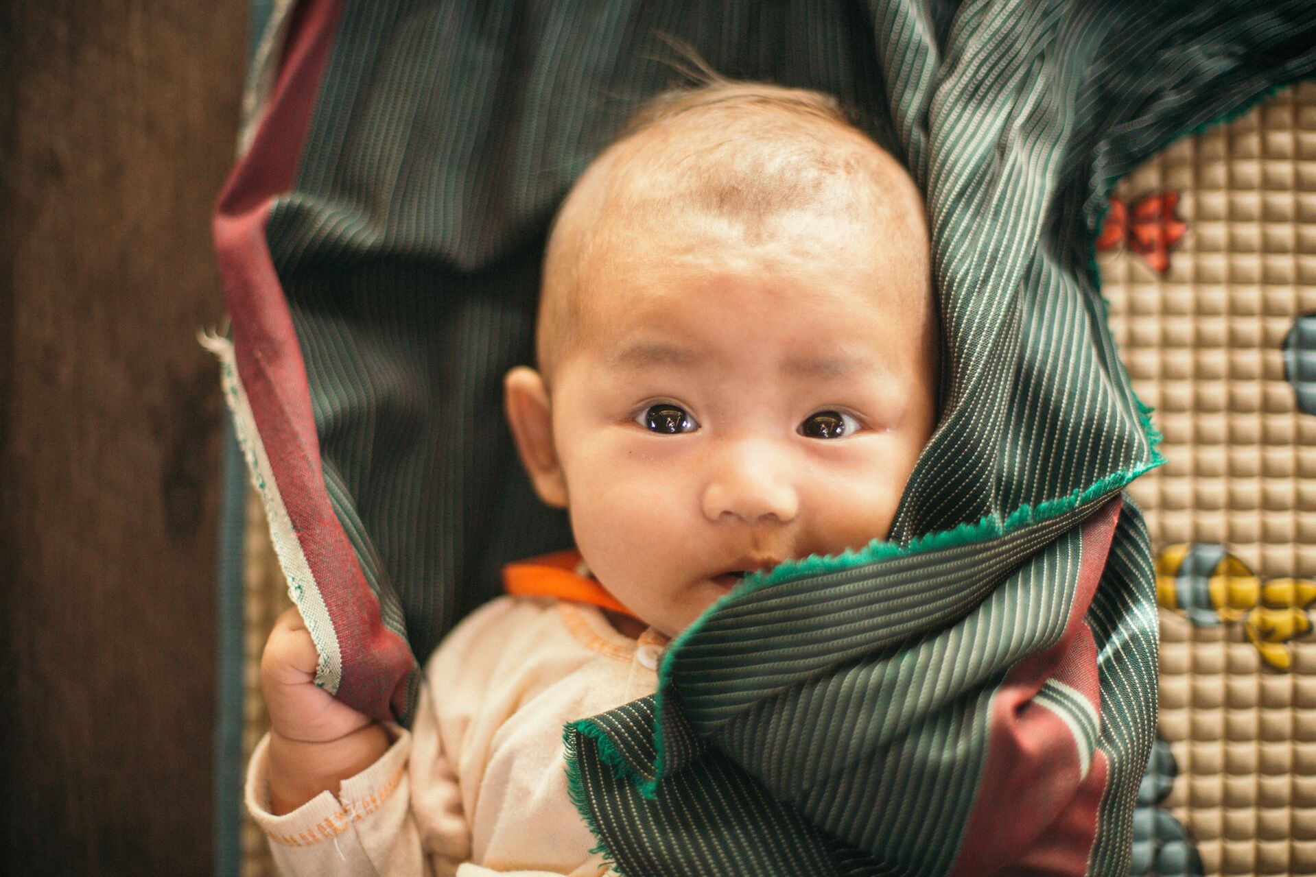 A close up of baby wrapped in a green and red blanket.
