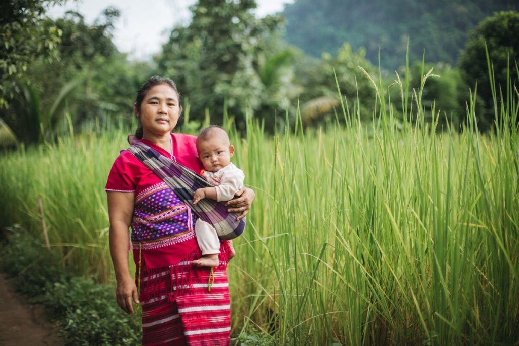 Muchunu and her granddaughter, baby Sathinee, outside their home in Thailand.