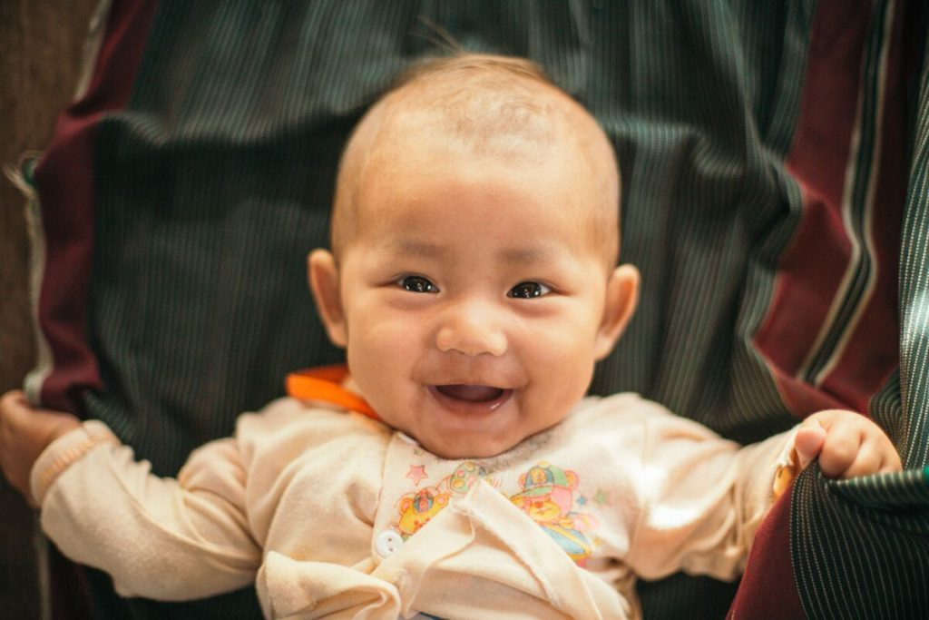 Baby Sathinee smiles big at the camera in a close up shot.
