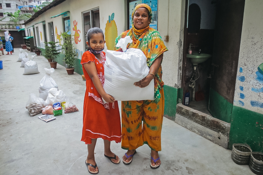 Mim is wearing an orange dress. She is standing with her mother, who is wearing a yellow, green, and brown outfit. Together, they are holding a white plastic bag full of food they received from Compassion. The Compassion building behind them is painted with a colorful mural.