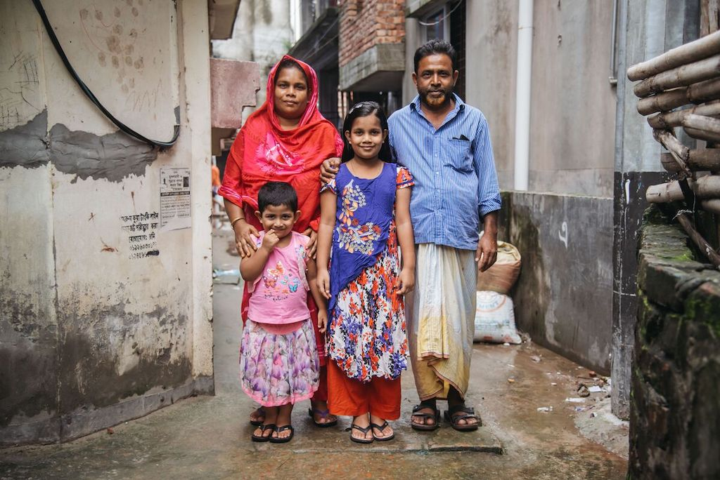 Mim is wearing an orange and purple dress. She is with her mother, wearing red, father, wearing a blue shirt and yellow pants, and her younger sister, wearing pink. They are standing outside their home with their arms around each other.