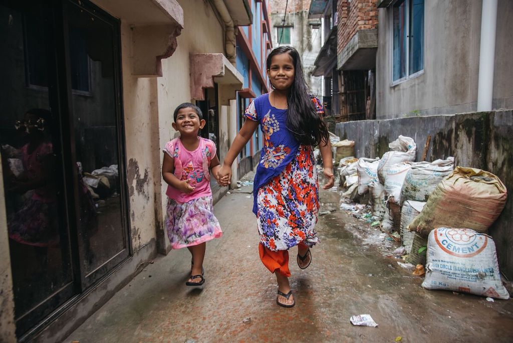 Mim is wearing an orange and purple dress. She is with her sister who is wearing a pink shirt and pink skirt. They are running together down an alley way. There are bags of cement along one side of the alley.