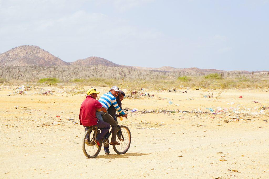 Three men ride on one bike through the desert