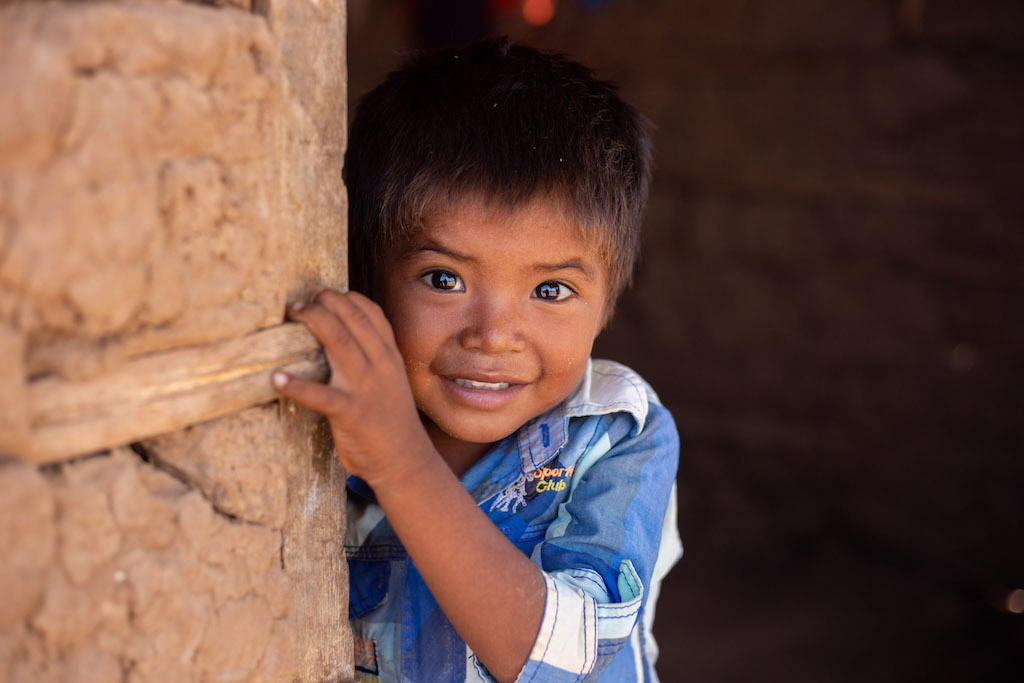 A little boy wearng a blue shirt peaks out of a wall smiling