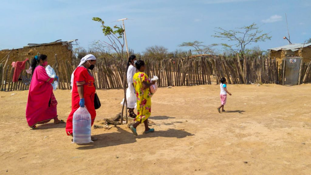 4 women are pictures arrying water and food packs through the desert.