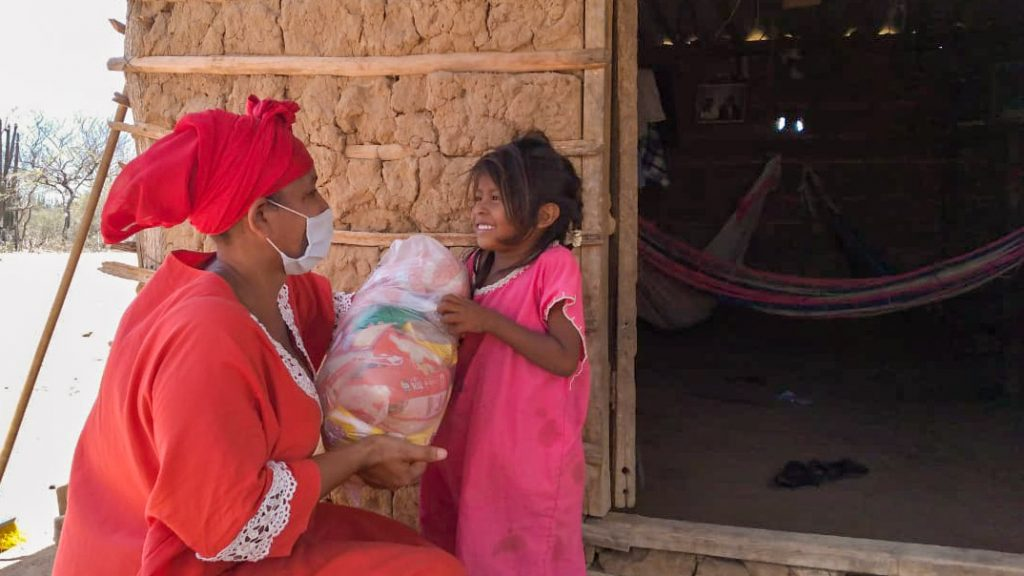 Pastor Enis delivers a food pack to a young girl.
