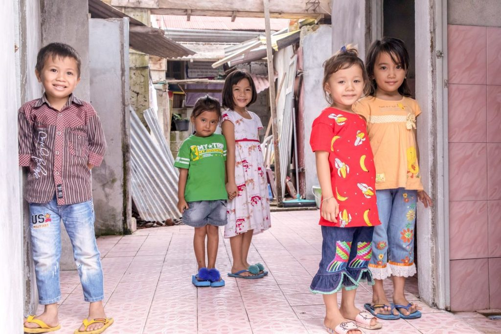 Children who attend the local Compassion centre in Tolombukan stand in front of the newly constructed toilets built by their family and neighbours and supported by Compassion.