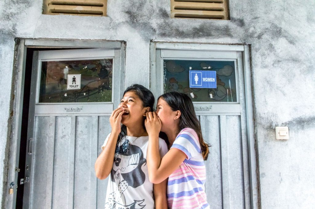 Siska and Anita, two teenage girls in Compassion's program stand in front of the new toilets located at their Compassion centre. Here, they can finally feel safe.